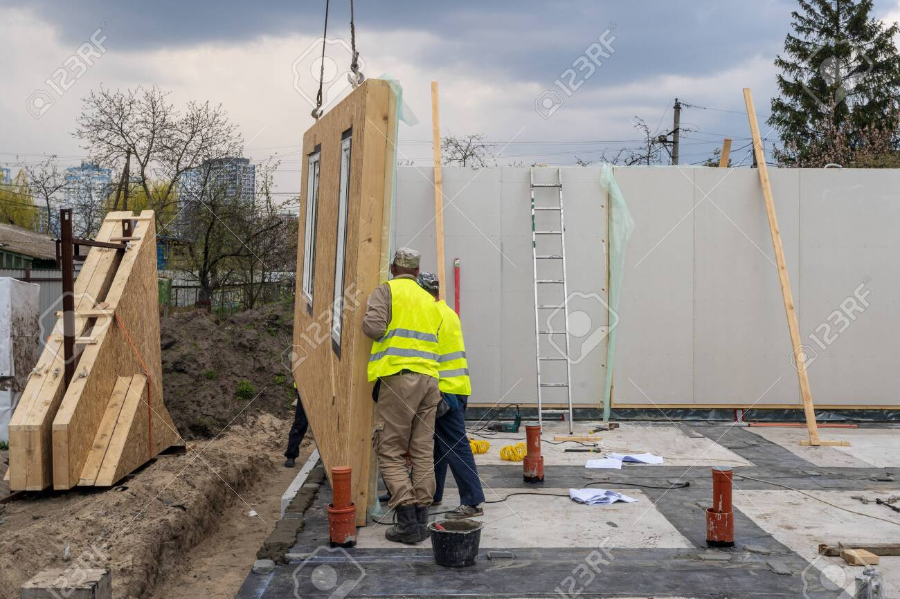 Process of construction new and modern modular house from composite sip panels. Two worker man in special protective uniform wear working on building development industry of energy efficient property - 129005493