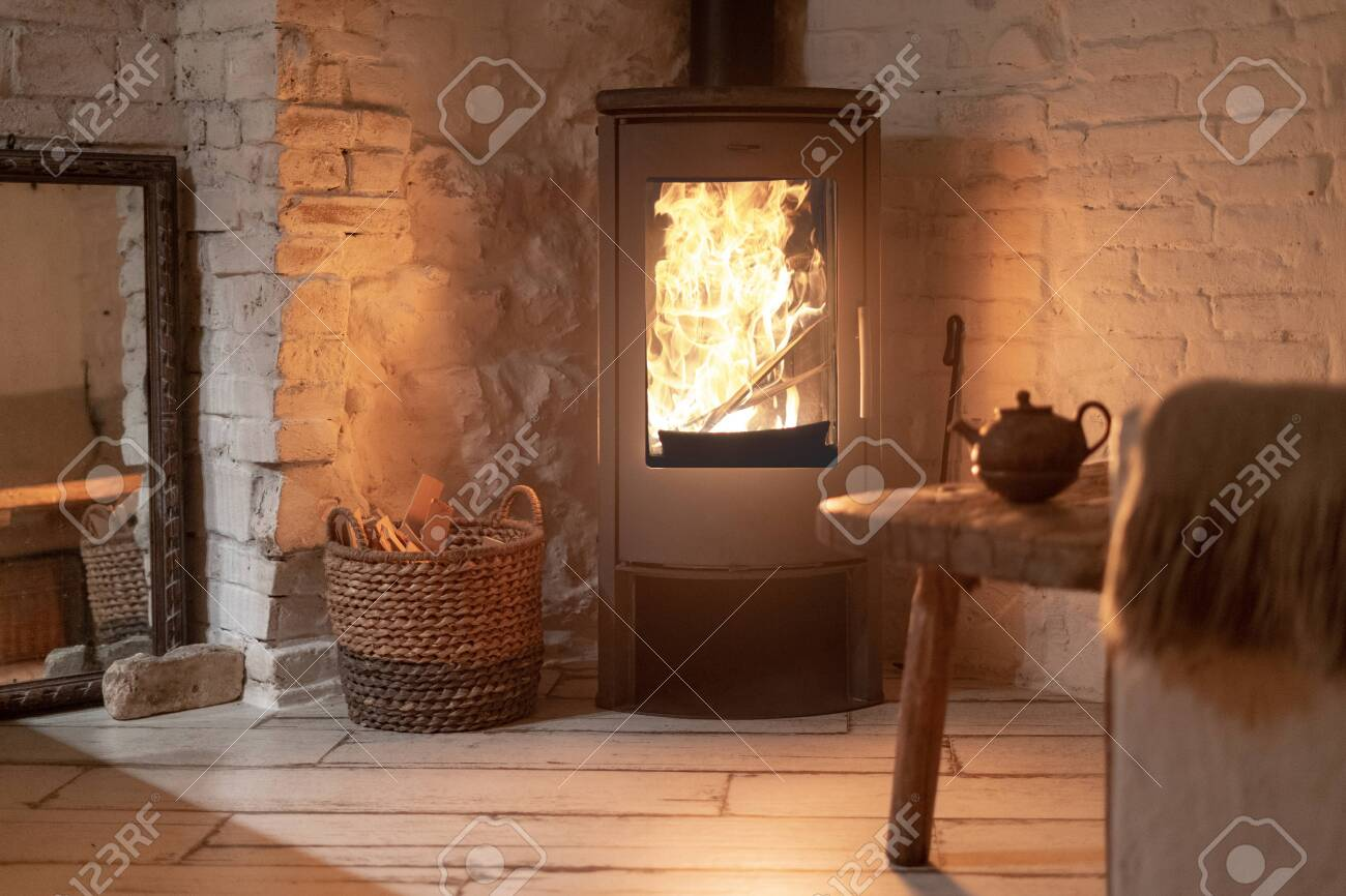 Table and teapot near wood stove fireplace in comfort house with cozy interior in room. Wicker basket with firewood near chimney with metal body and glass door - 130719641