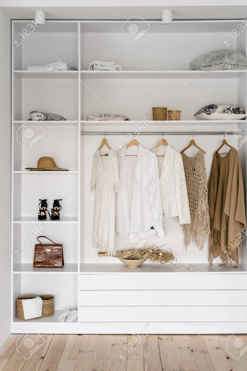 Vertical photo of modern and open garderobe in dressing room..