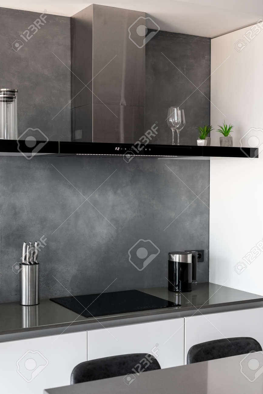 Contemporary clean kitchen with glossy furniture, countertop with black chairs next to it, black induction cooktop with exhaust hood above it, useful technology and home appliances. Vertical shot - 173398455