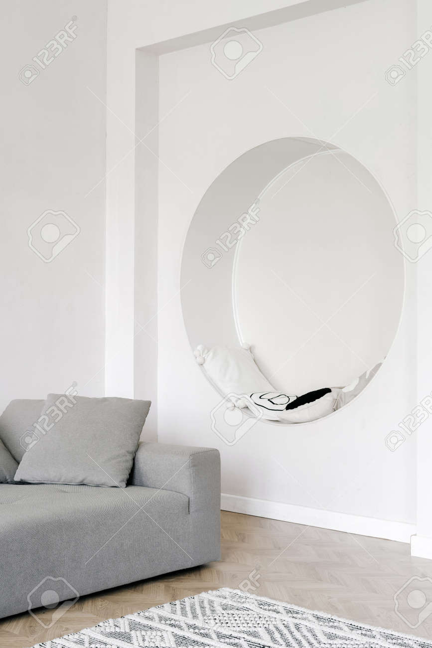 Living room interior, home design in white. Modern apartment style, minimal decor in house. Cozy flat with nobody. White wall with circle niche with pillows, space for relax. - 173398435