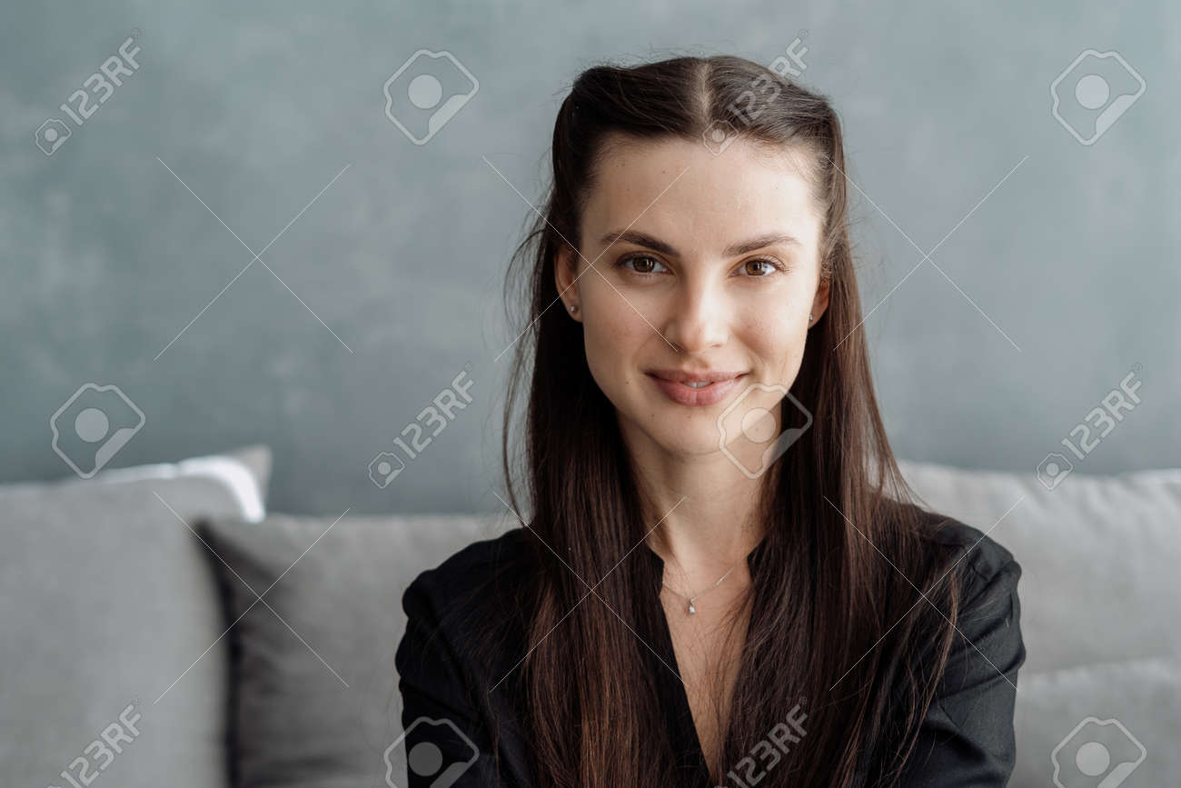 Portrait of young charming brunette woman looking at camera with smile while sitting on couch and spending great time at home, headshot of beautiful friendly female indoors - 173398074