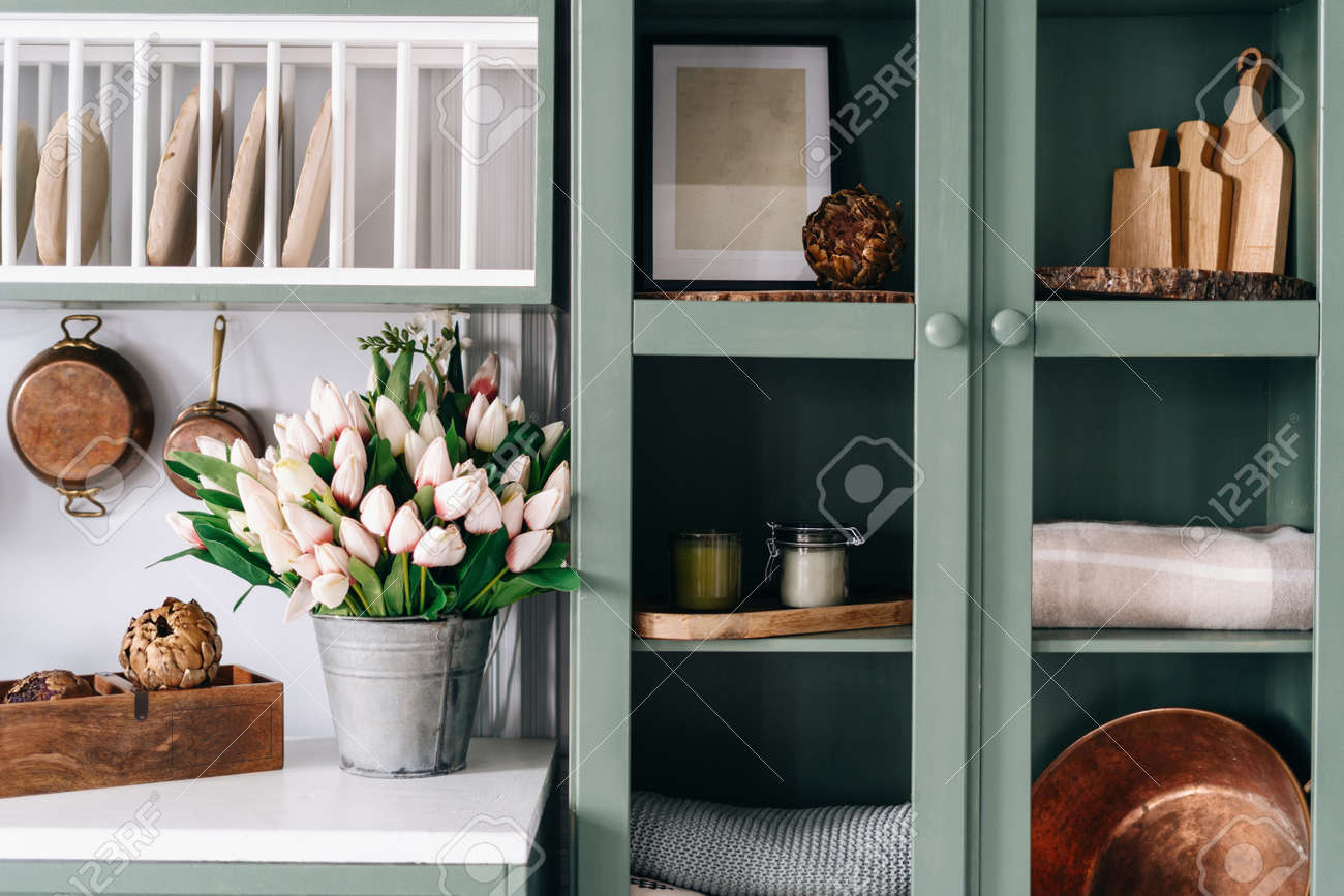 Green vintage cupboard with glass doors, set of various sized wooden cutting boards and tablecloths, countertop with white surface, lots of flowers in metal bucket, comfortable kitchen enviroment - 173398300