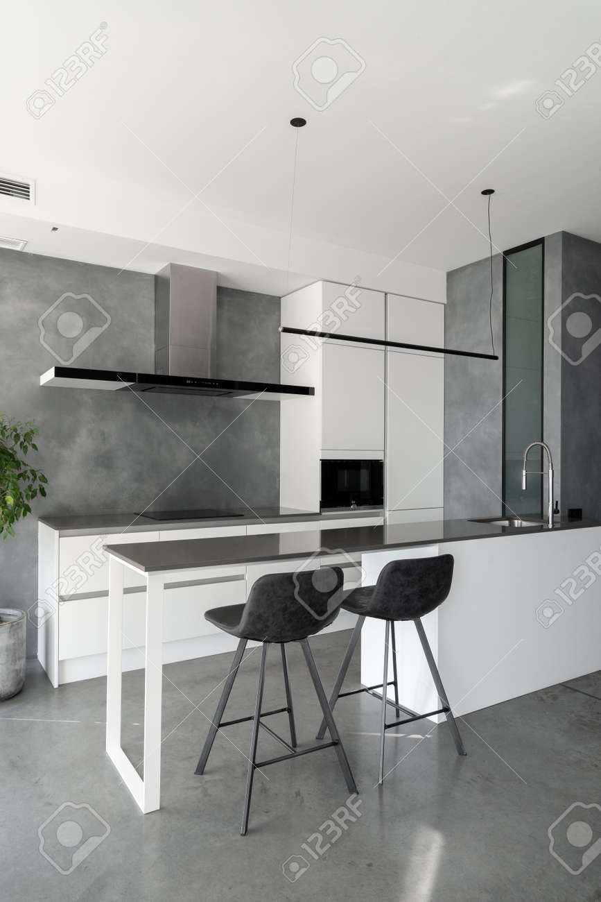 Spacious kitchen with minimalist square shaped furniture, gray floor and walls, counter with integrated sink and pair of bar stools in front of it, built-in microwave and cooktop. Vertical shot - 173398365