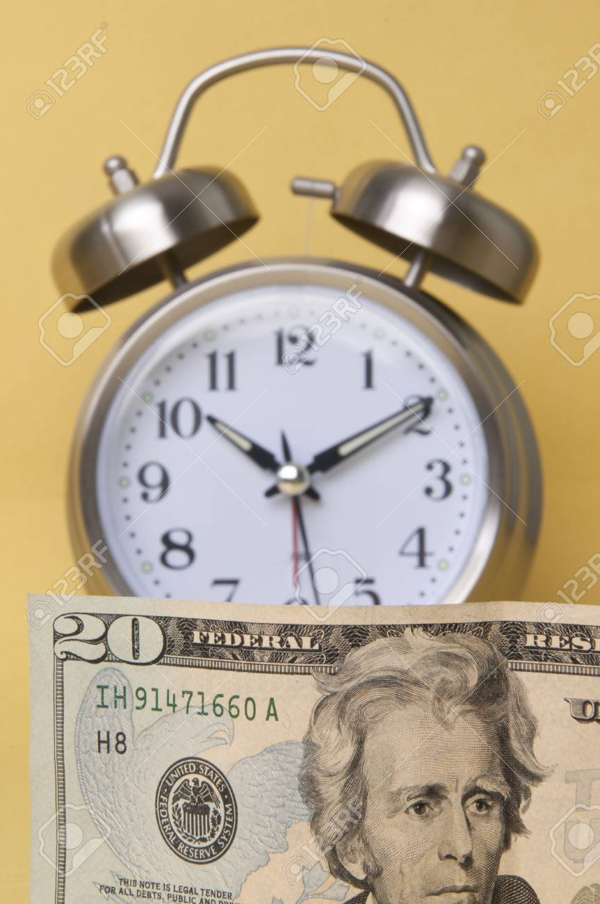 In today's world time is money.  Alarm clock and American paper currency isolated on a yellow background. Stock Photo - 5925958