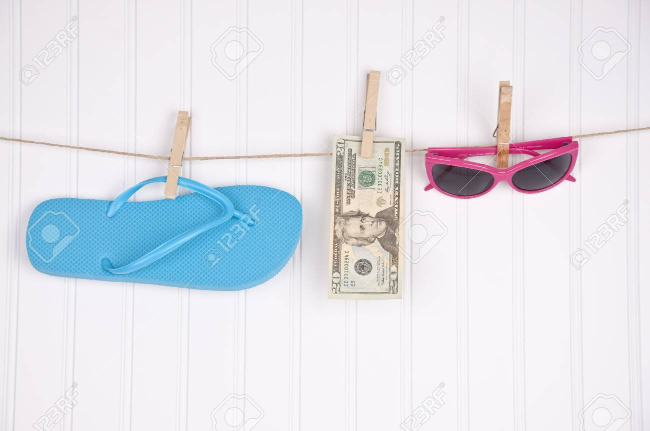 Fashion objects and money on a clothesline to represent the cost of summer fashion. Stock Photo - 6881905