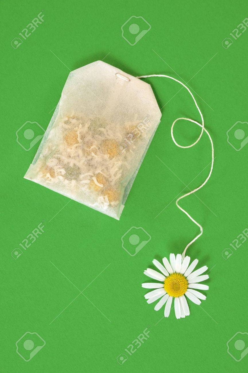 Bag of chamomile tea over green background - concept Stock Photo - 10618822