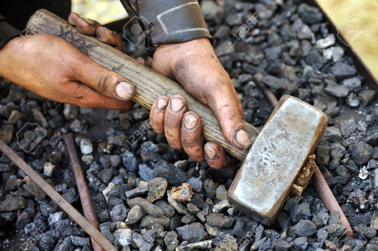 Detail of dirty hands holding hammer - blacksmith Stock Photo - 11274802