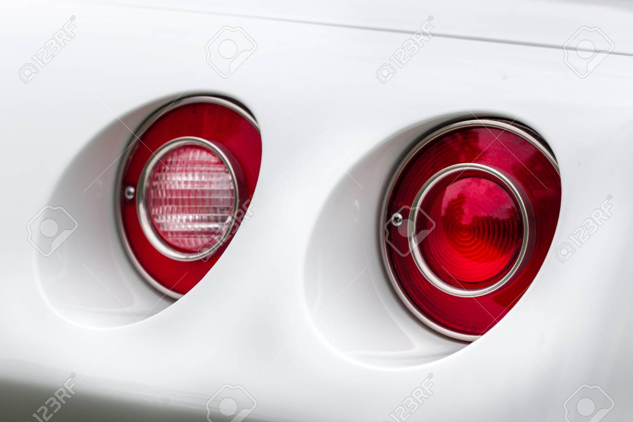 Close-up of red tail lights of a white shiny classic vintage