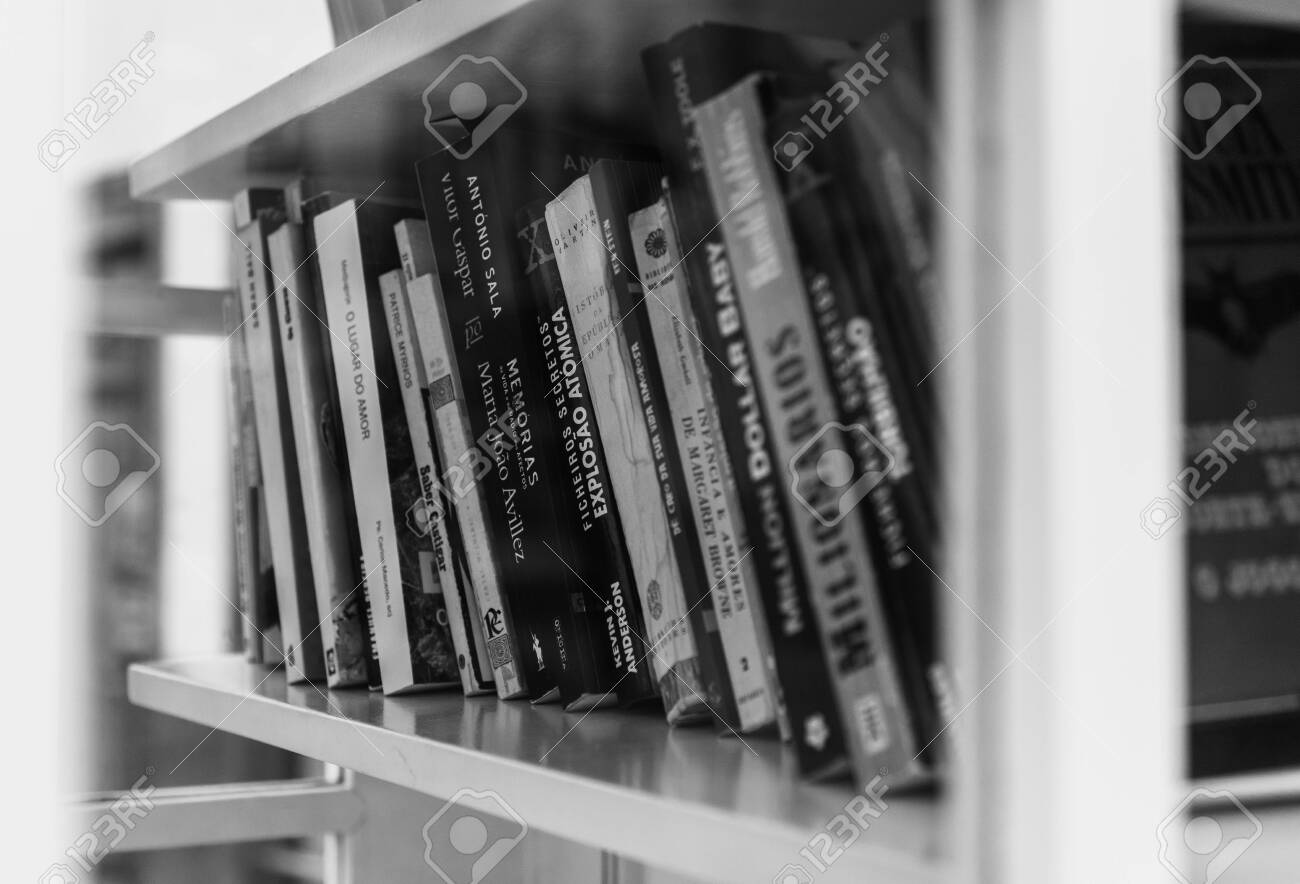 A black and white picture of a group of books sitting on a shelf inside a phone booth. - 132811191