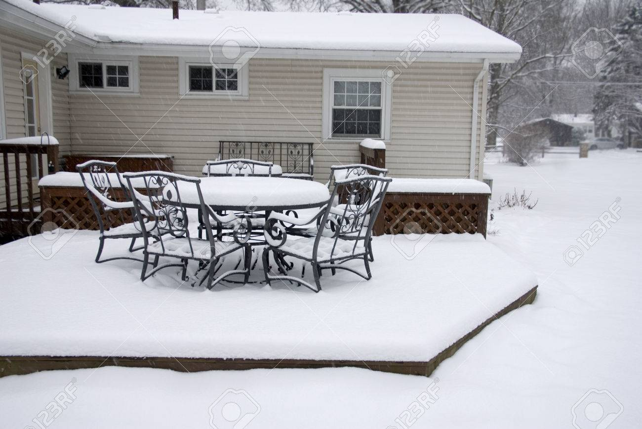 a backyard deck covered in snow during a blizzard stock photo