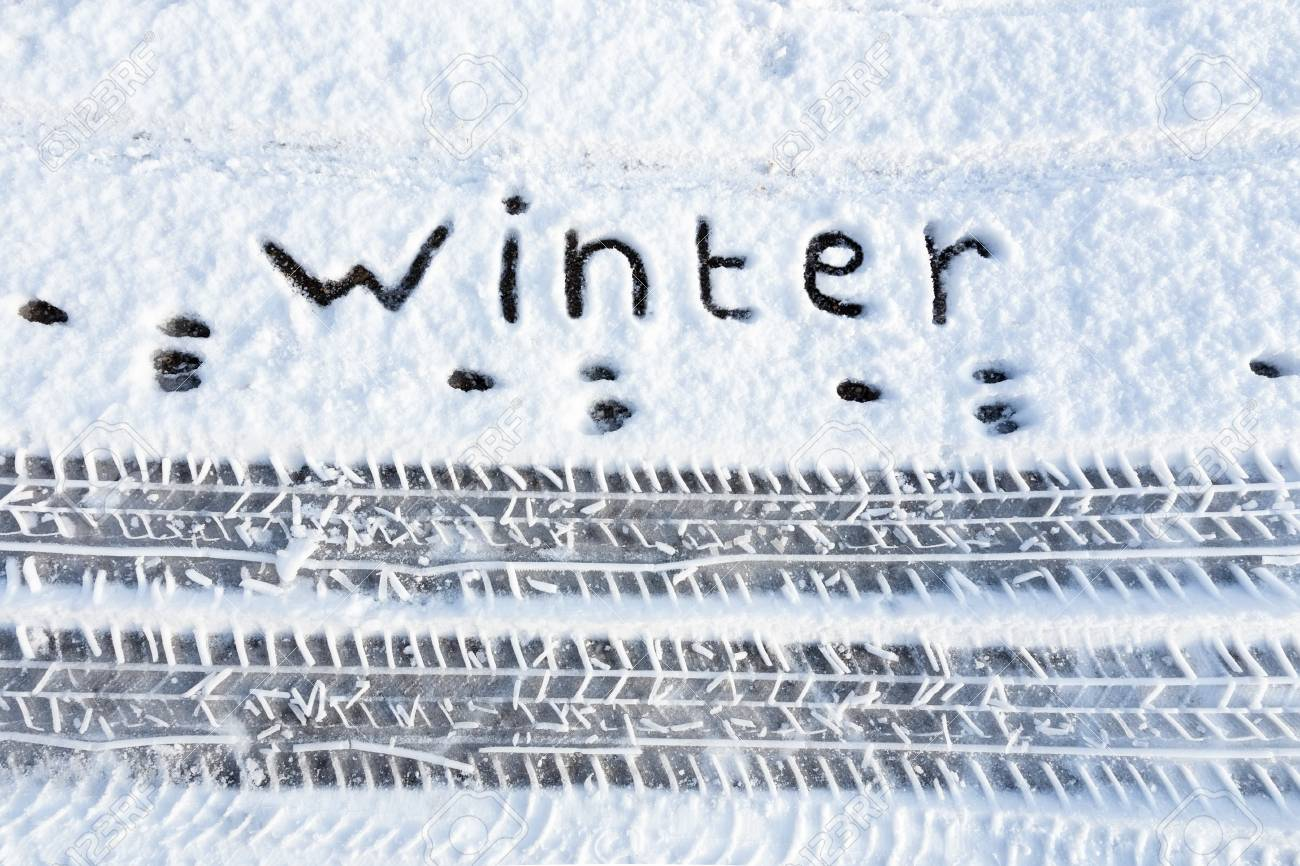 Word winter and tire tracks in snow during winter season - 42355332