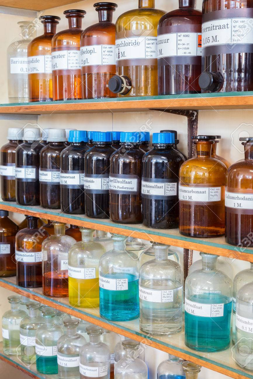 Rows of chemicals in bottles on shelves at chemistry on high school - 67975352
