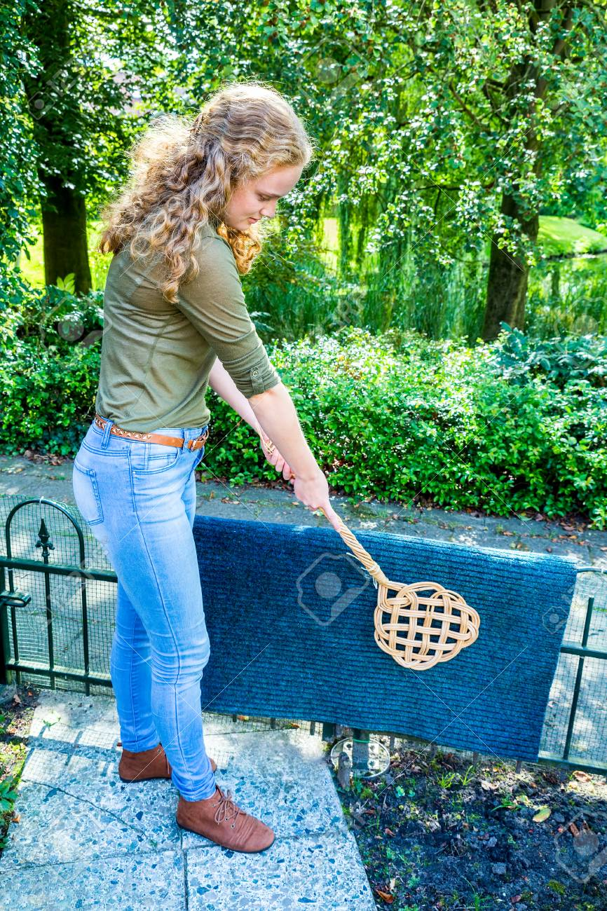 Stock Photo - Young caucasian woman beating door mat with carpet beater outside