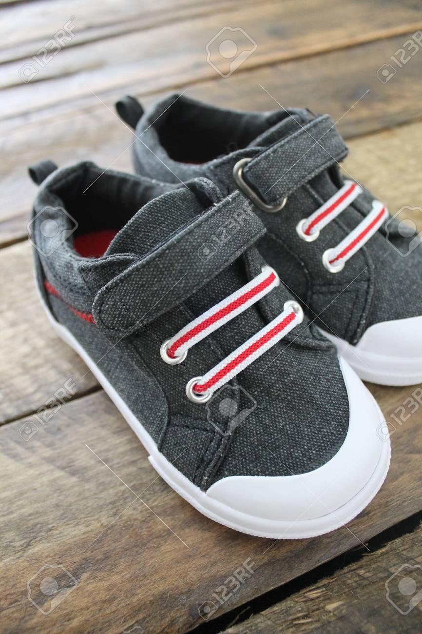 6fbd9f4617 Foto de archivo - Zapatos para niños pequeños aislados en un fondo de madera