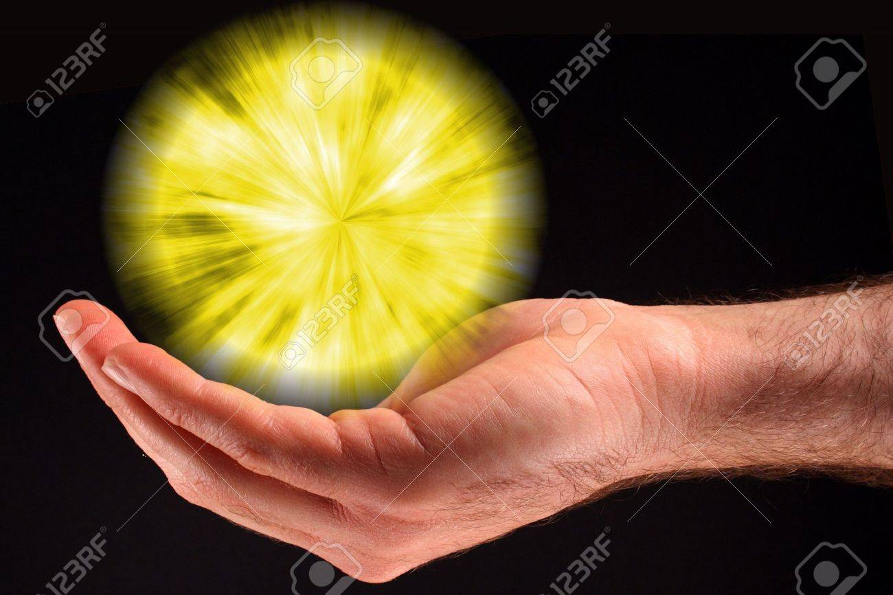 A hand holding a yellow ball of light against a black background. Stock Photo - 5871485