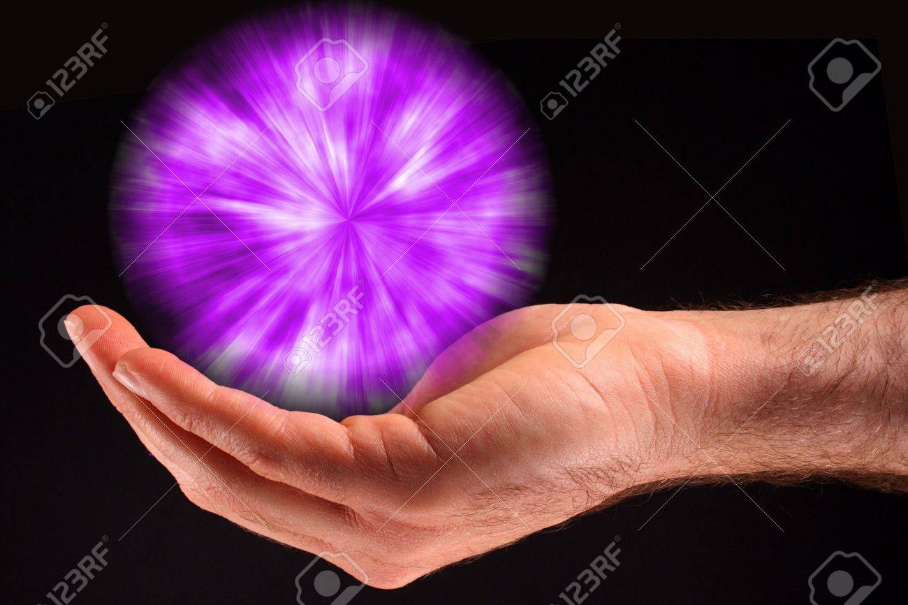 A hand holding a purple ball of light against a black background. Stock Photo - 5871493