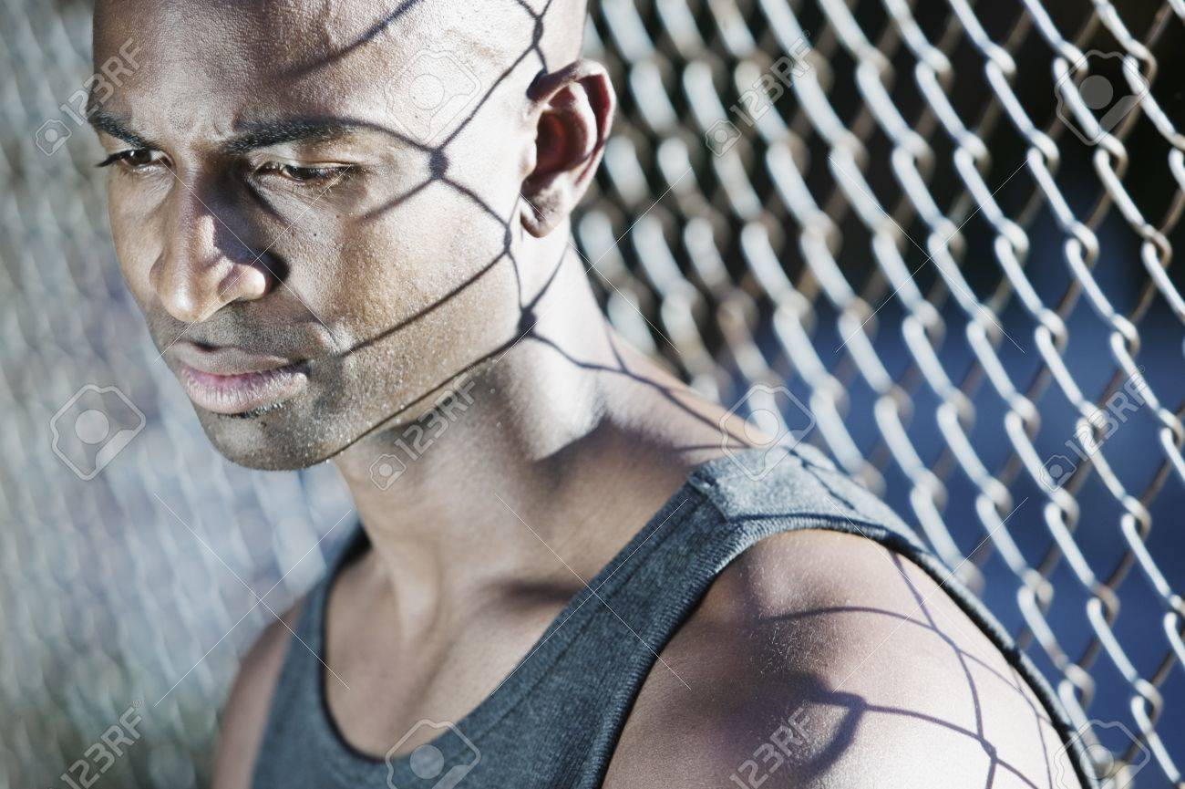 Man sitting next to a chain-link fence looking down Stock Photo - 16043458