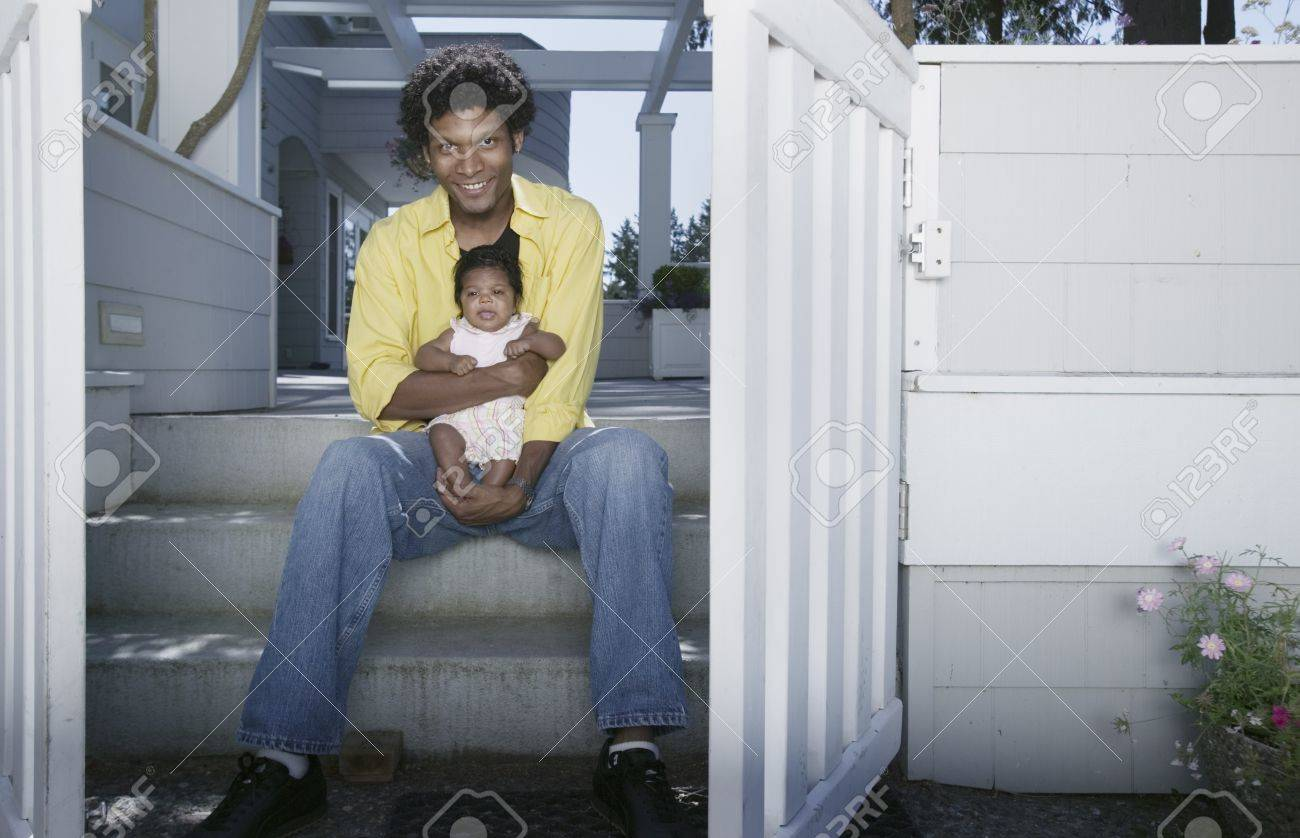 Man sitting on stairs of a house holding a baby Stock Photo - 16043602