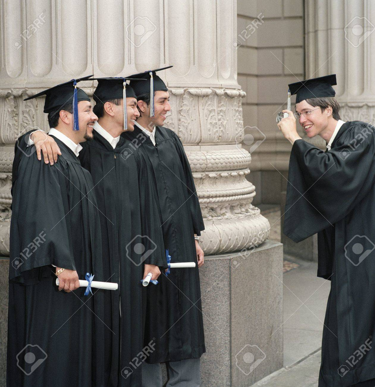Young male graduate photographing three male graduates Stock Photo - 16044186