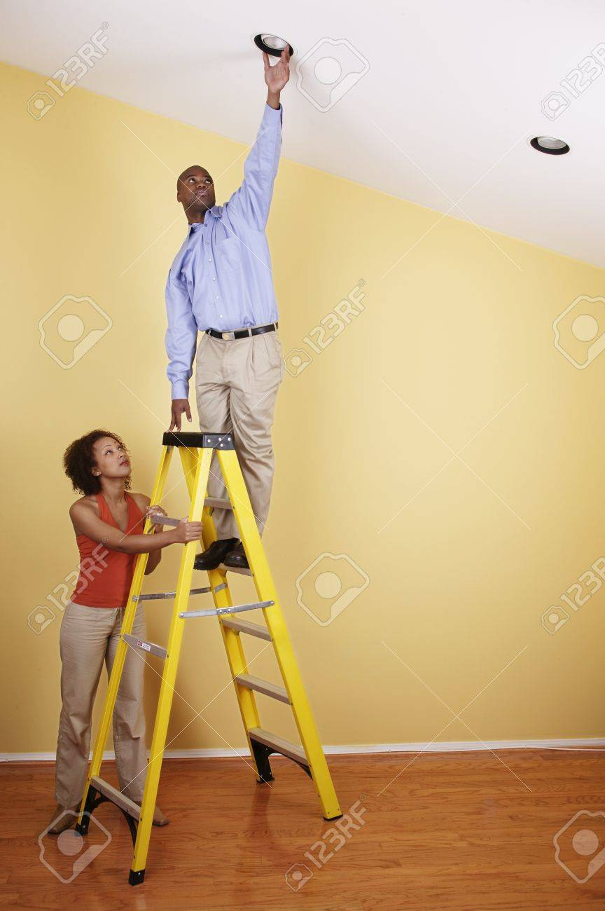 Young man standing on a ladder with a young woman standing beside him Stock Photo - 16044434