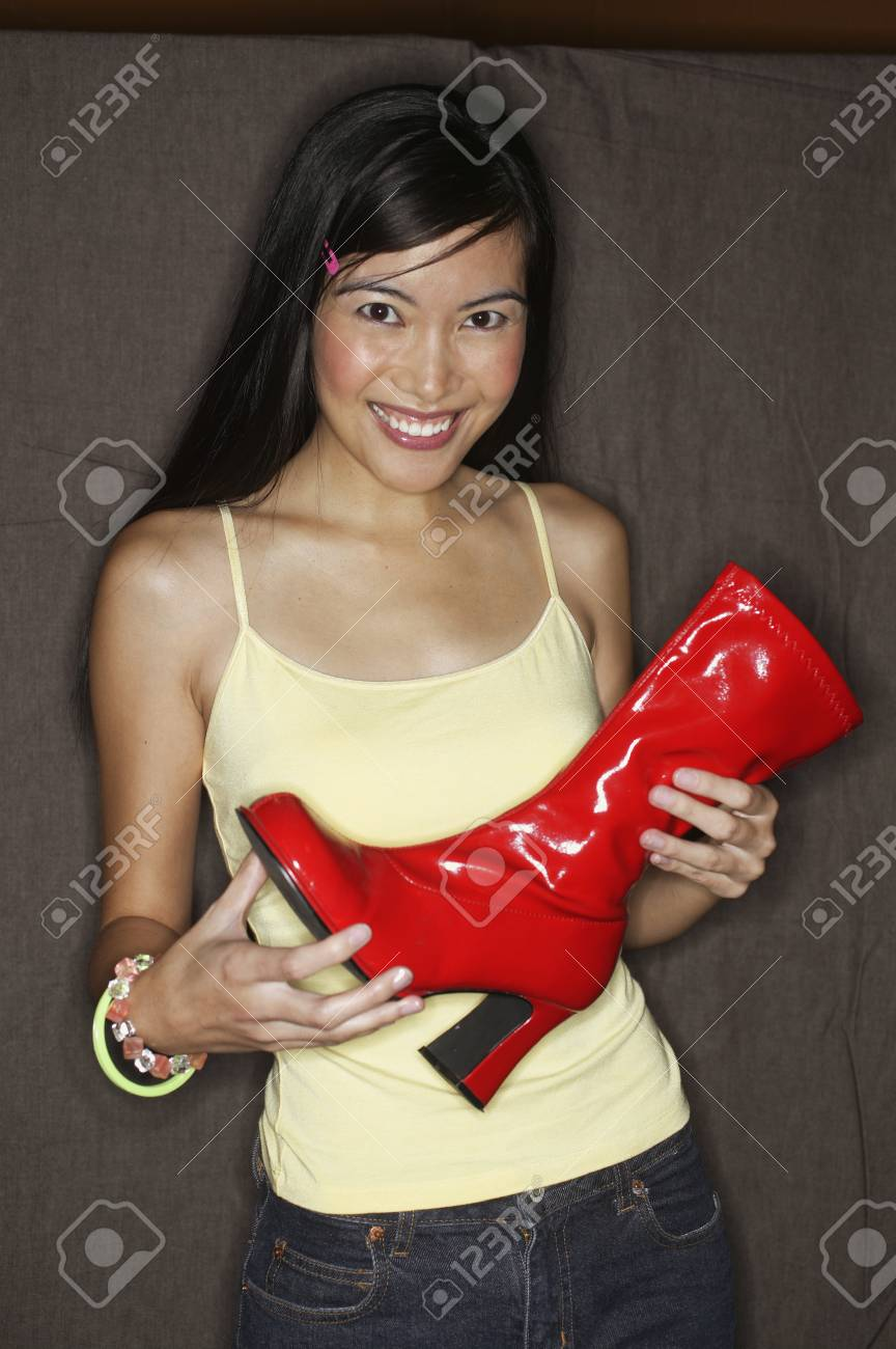 Close-up of a young woman holding a red leather boot in a department store Stock Photo - 16044468