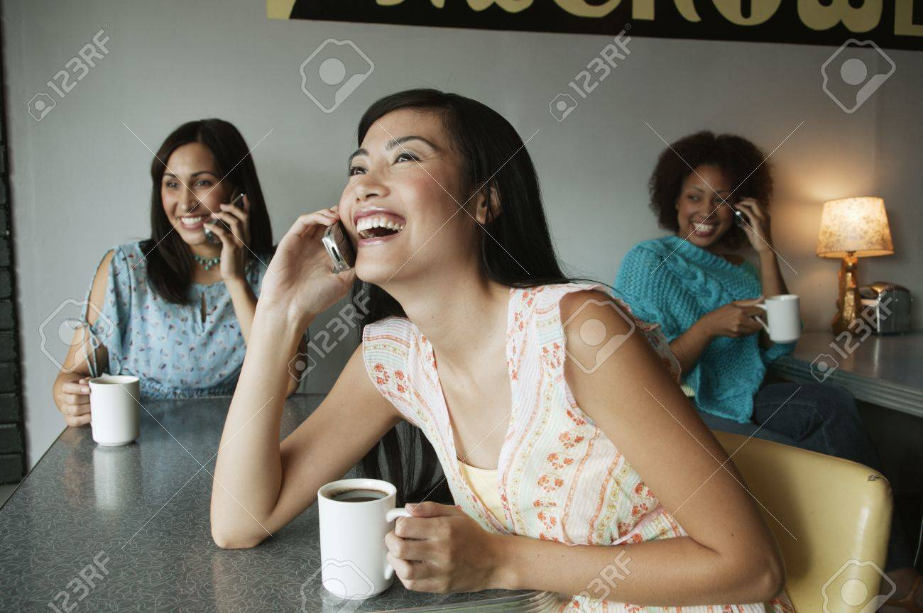 Three young women talking on mobile phones Stock Photo - 16044491