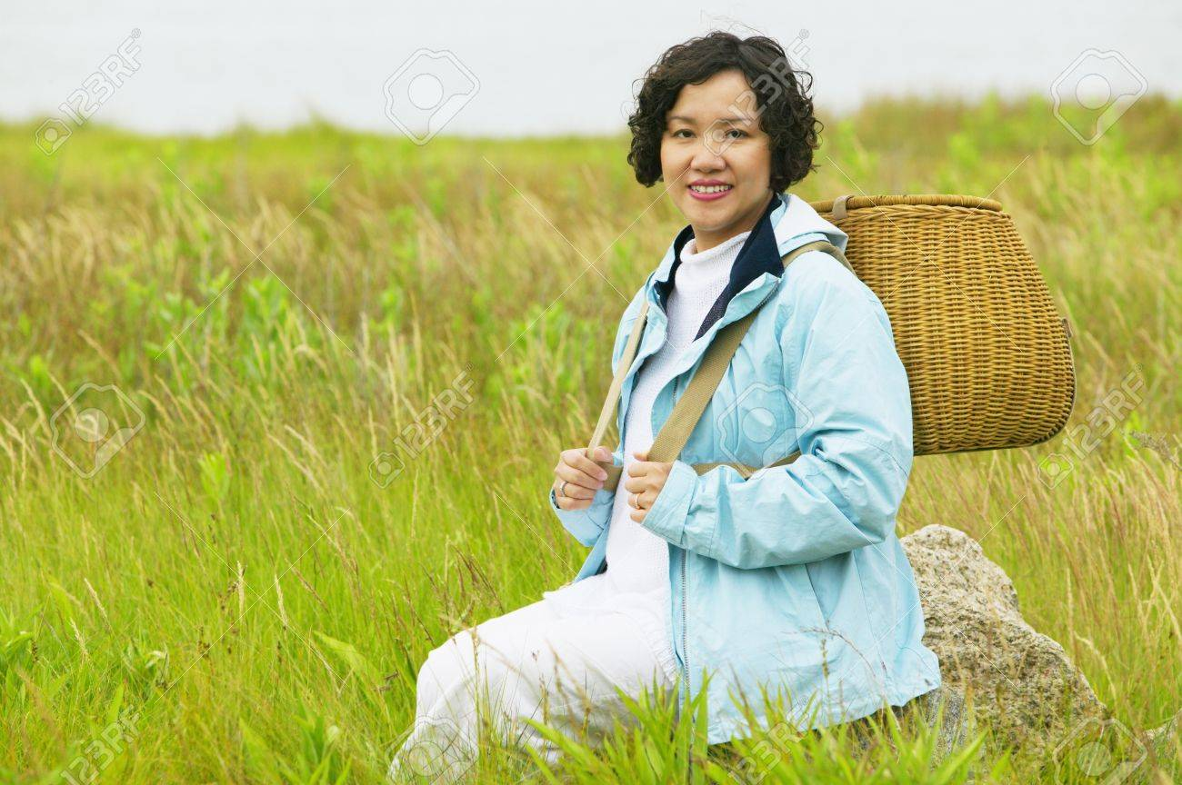 Mid adult woman sitting in tall grass holding a basket Stock Photo - 16044787