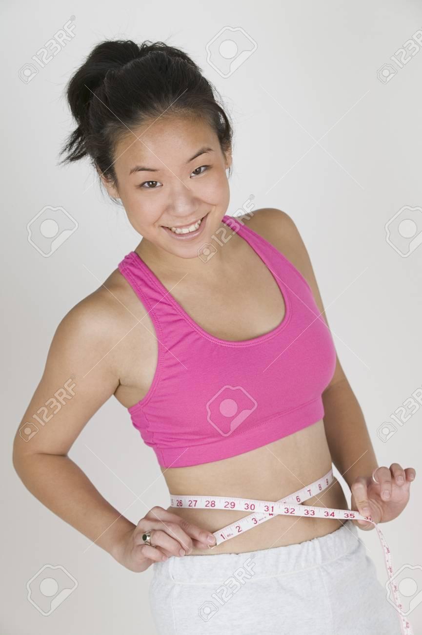 Portrait of a teenage girl measuring her waist Stock Photo - 16045058