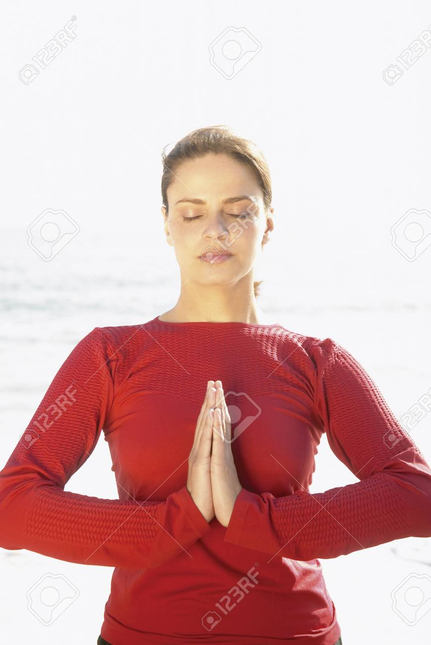 Young woman meditating on the beach Stock Photo - 16045179