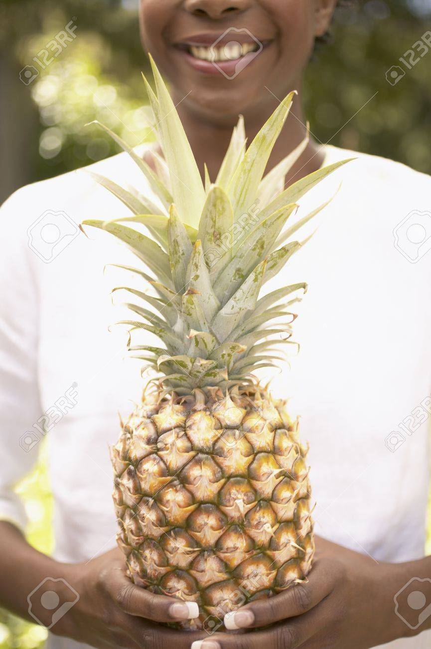 Woman holding a pineapple at a garden Stock Photo - 16045247