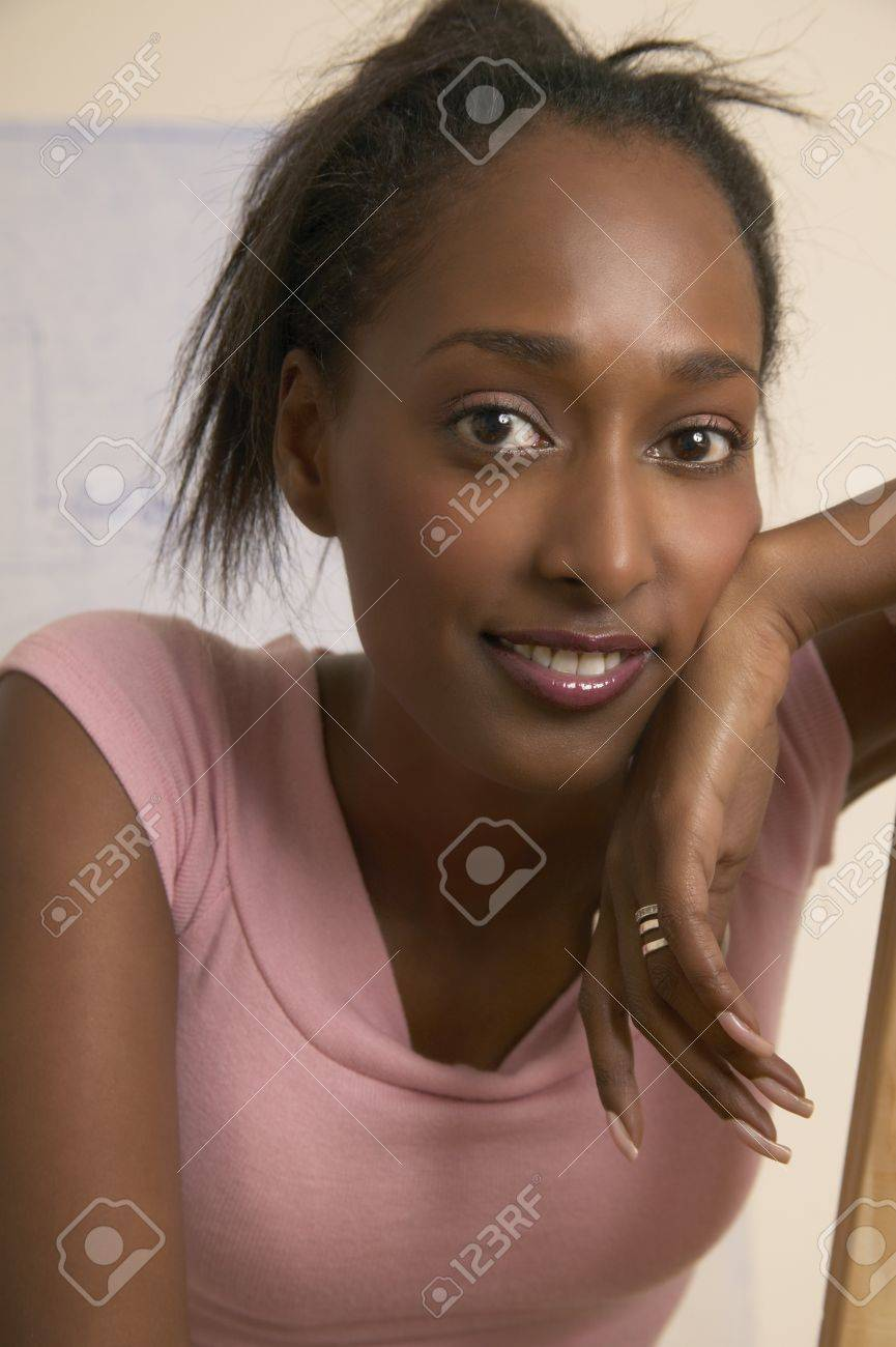 Portrait of a young woman sitting with hands on cheeks Stock Photo - 16045274