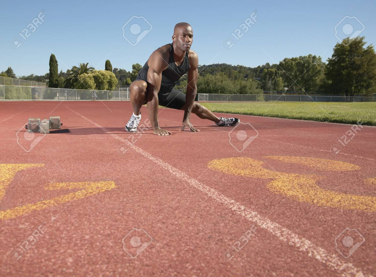 Young man stretching on a running track Stock Photo - 16045471