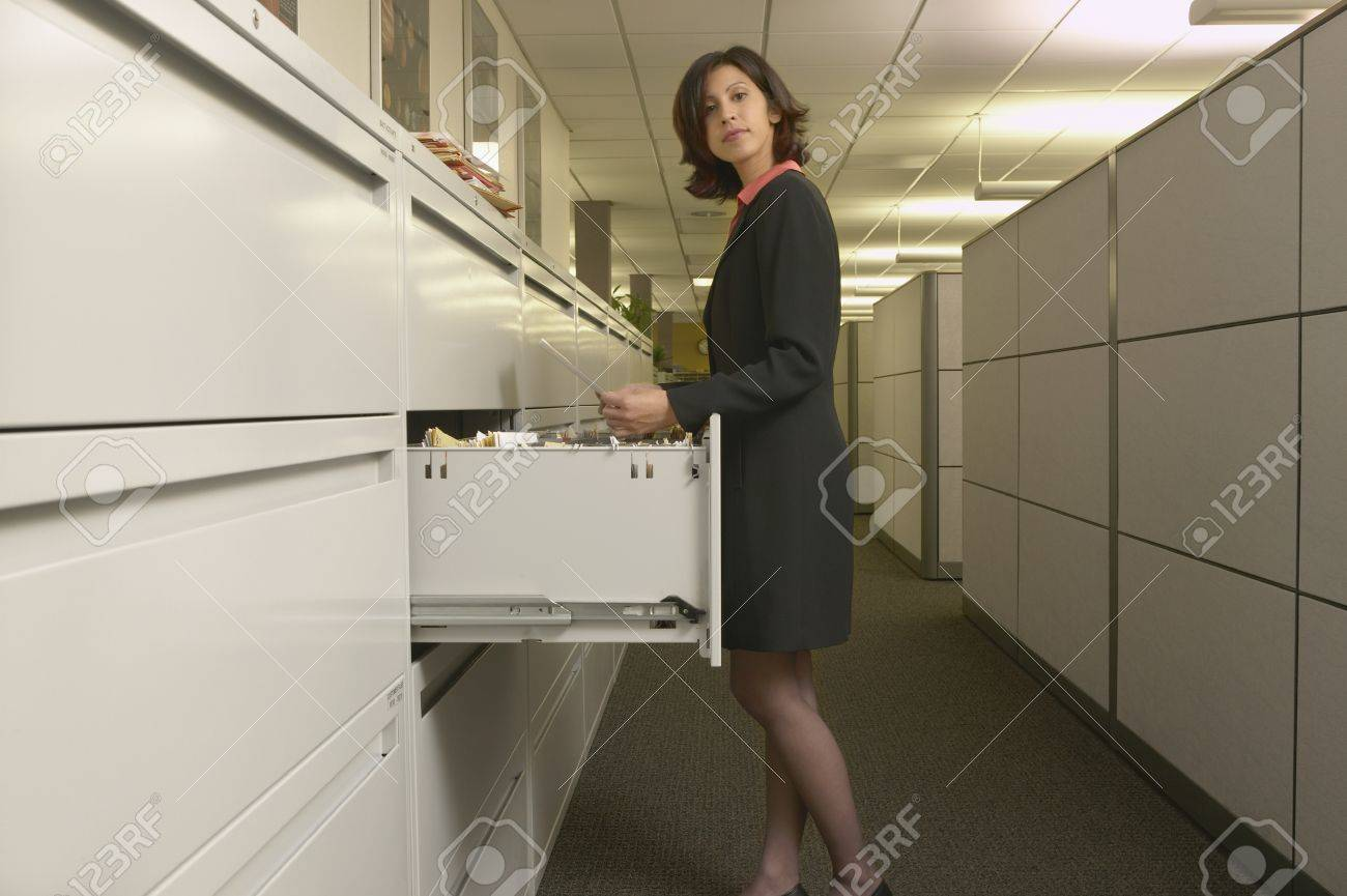 Young woman standing in front of a filing cabinet Stock Photo - 16046235