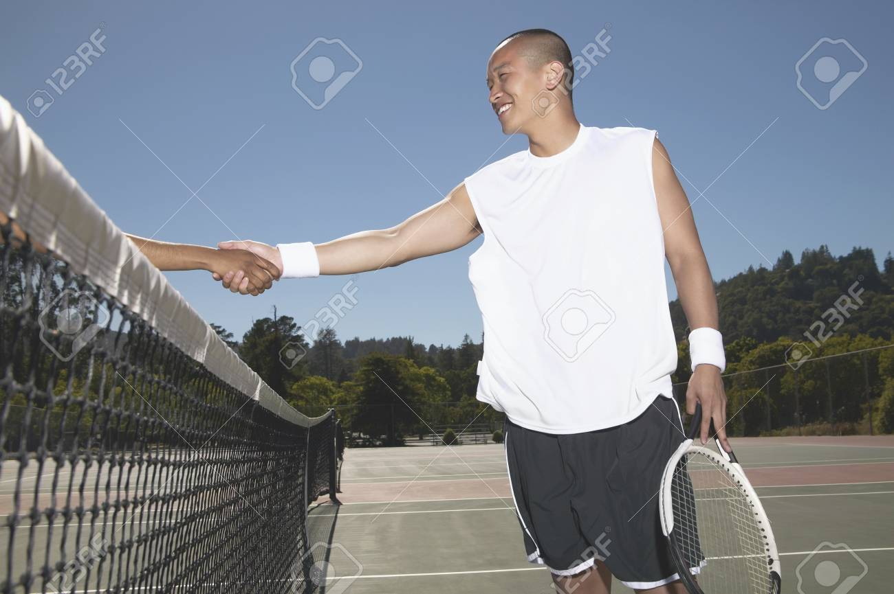 Young man shaking hand with a woman over a tennis net Stock Photo - 16046568