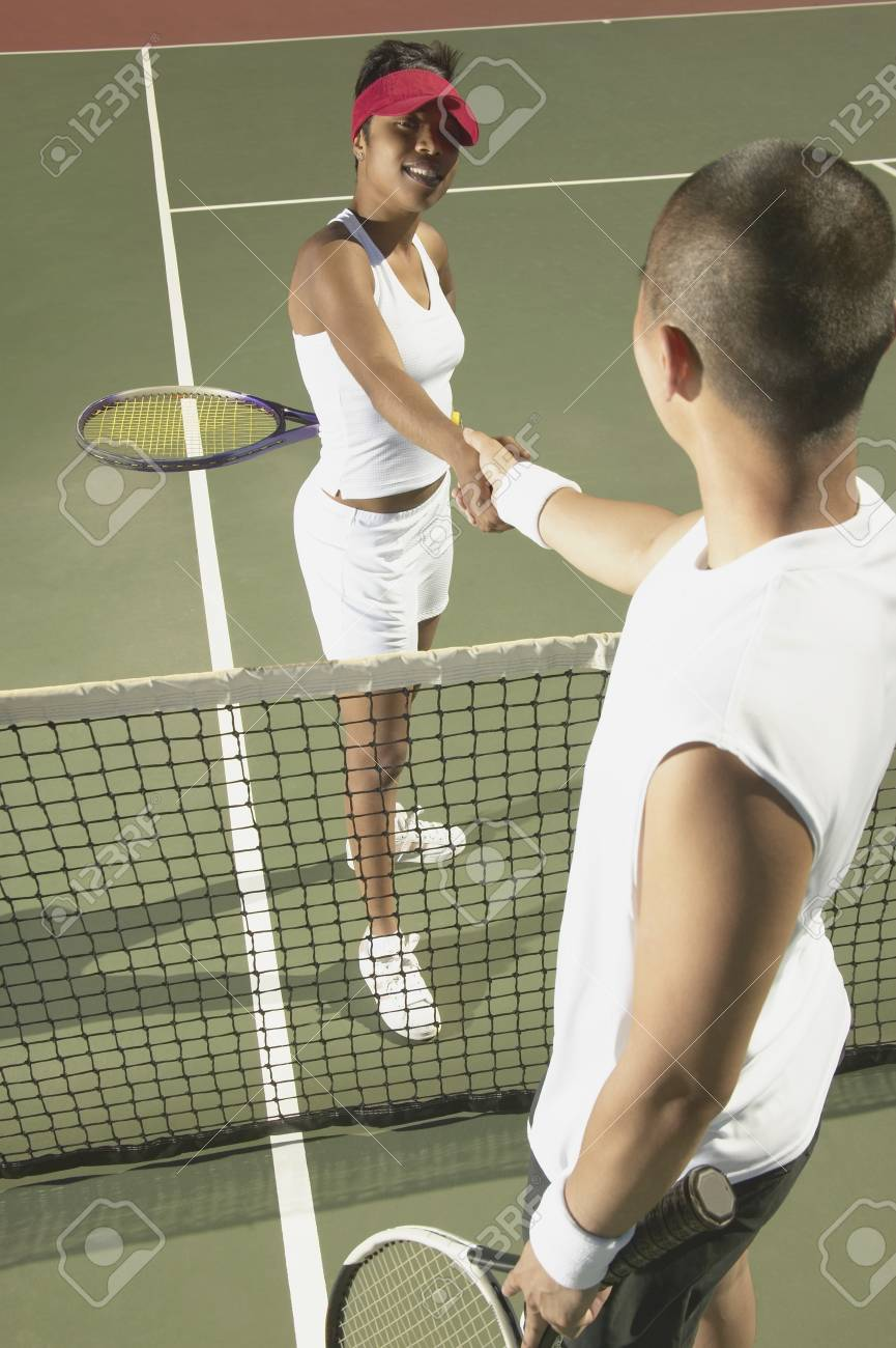 Young man and a young woman shaking hands over a tennis net Stock Photo - 16046555