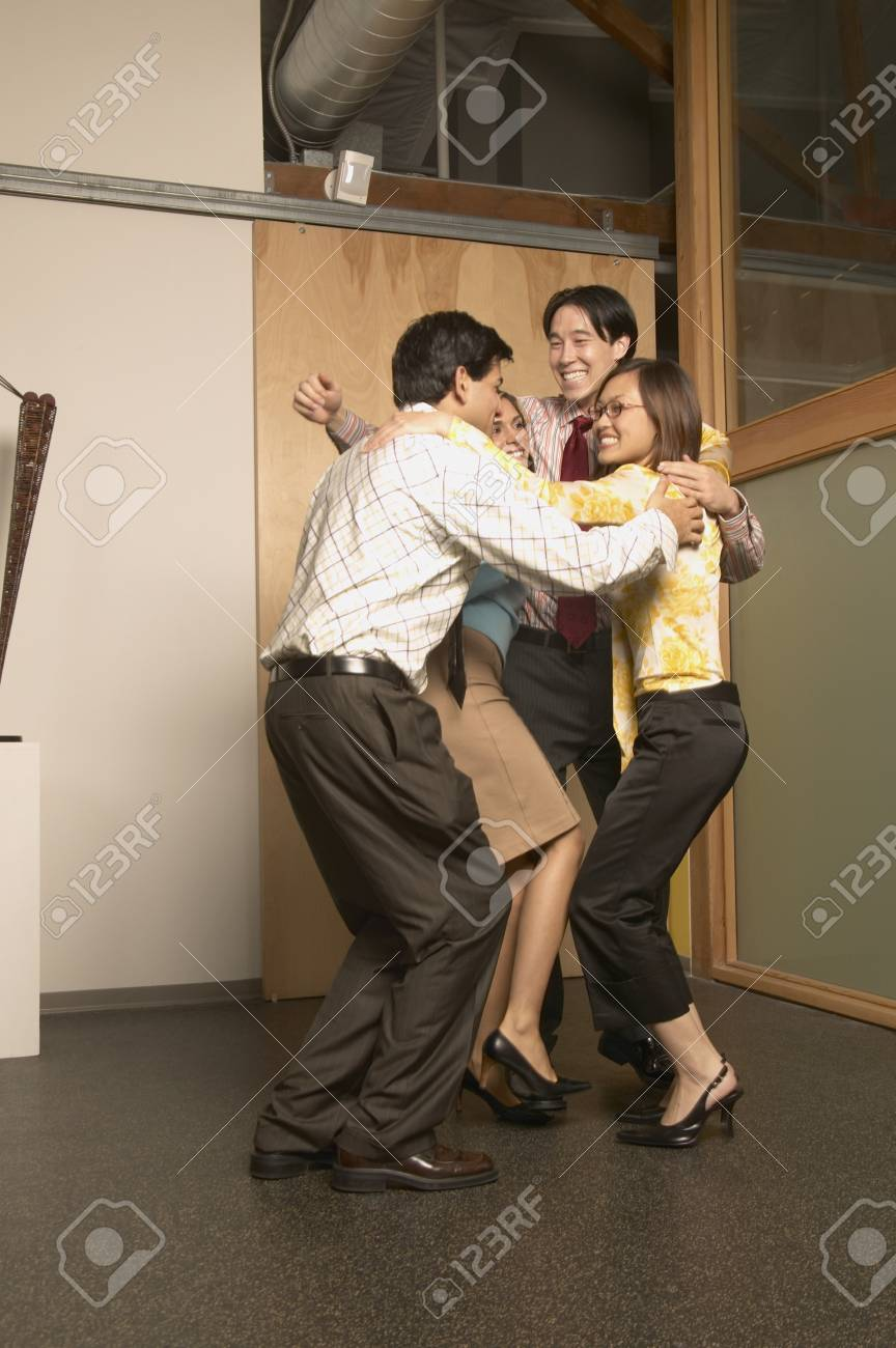 Four business executives celebrating in an office Stock Photo - 16047612