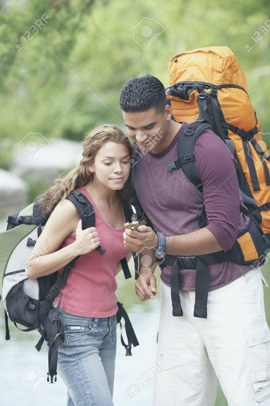 Hiking couple consulting a compass Stock Photo - 16070746
