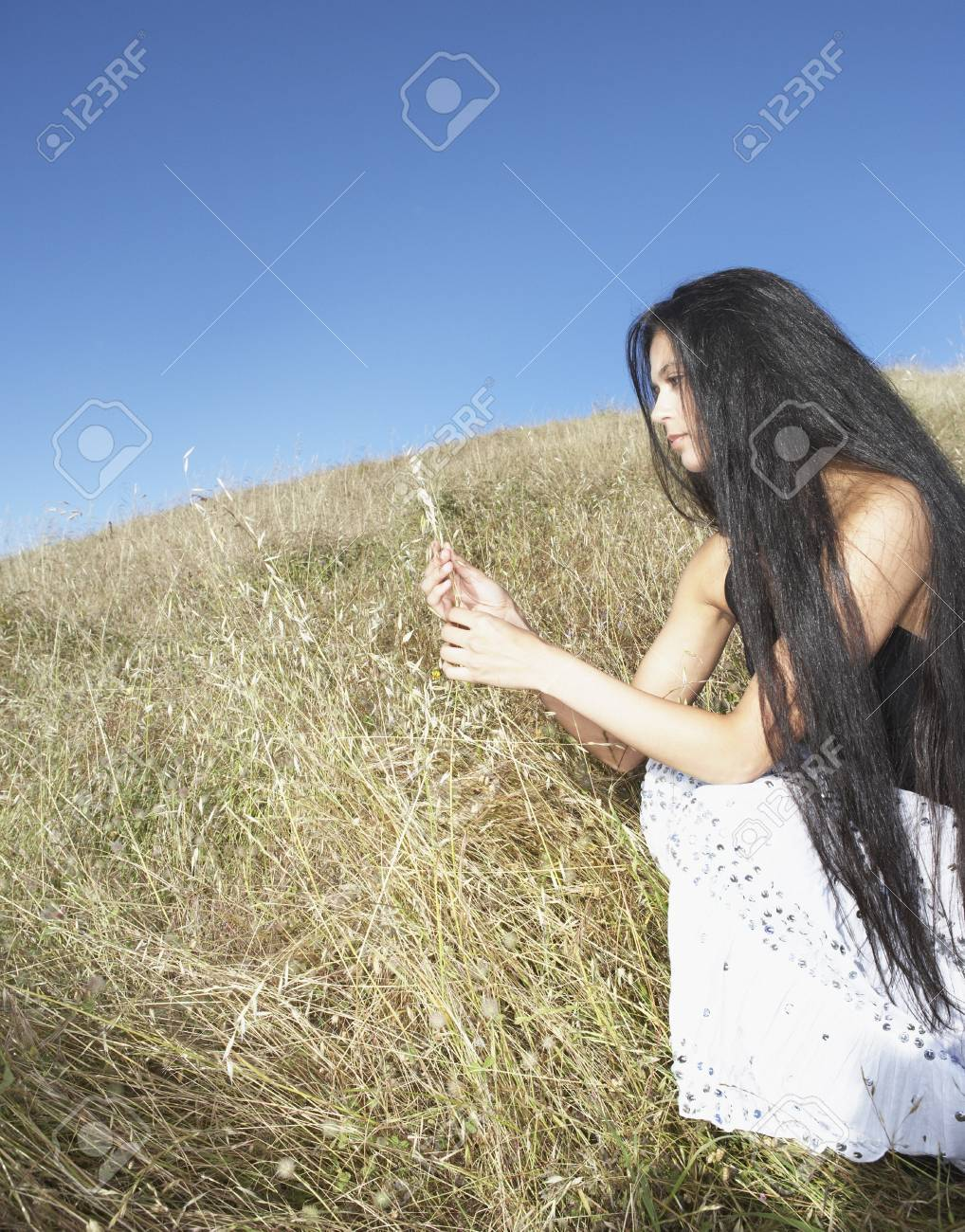 Woman sitting in grassy field Stock Photo - 16071402