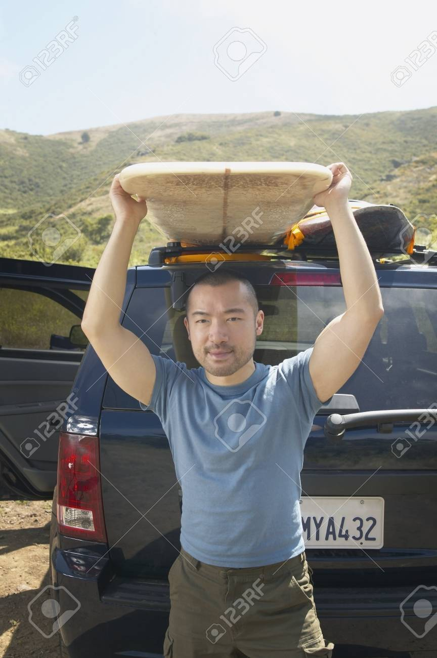 Man lifting surfboard from car rack Stock Photo - 16071440