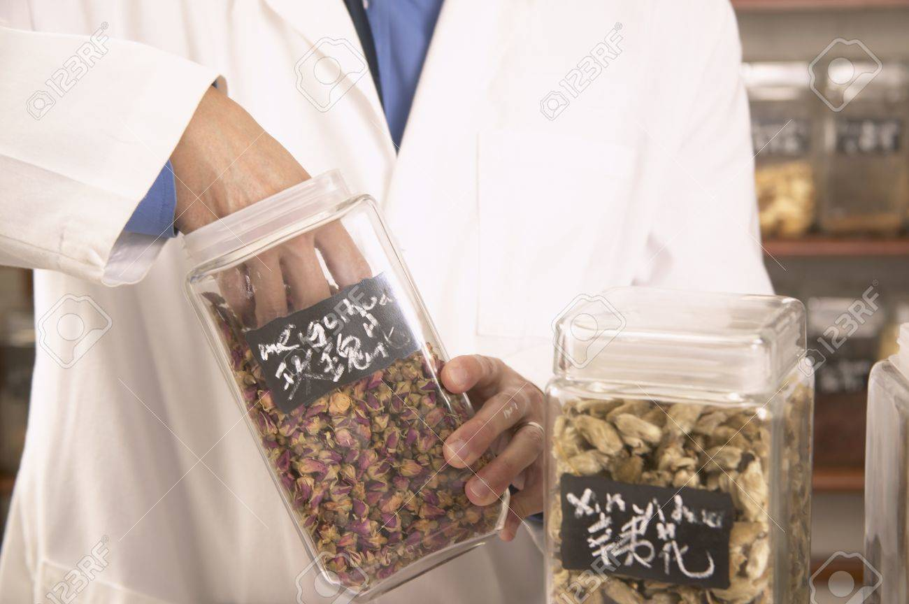 Doctor taking out herbs from a jar Stock Photo - 16071534