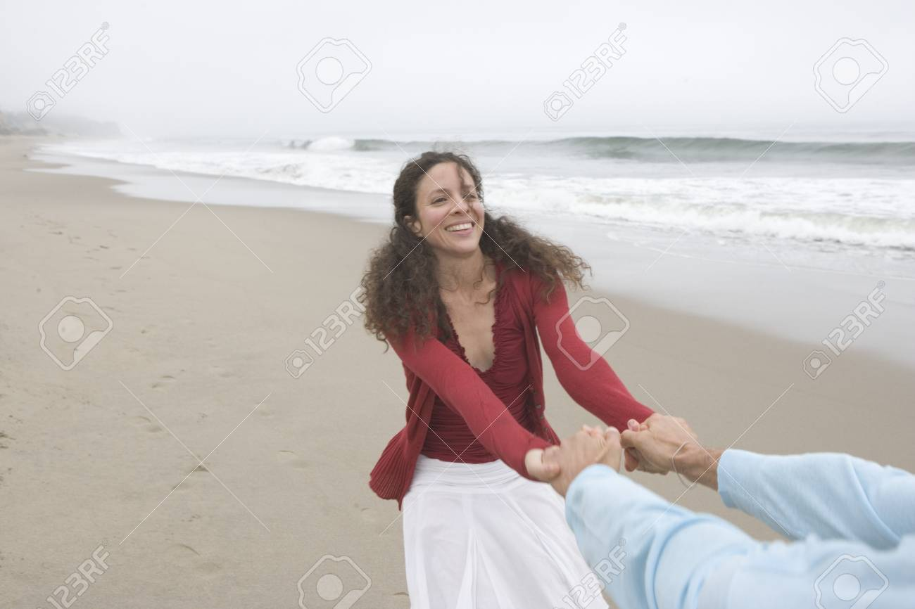 Woman pulling her boyfriend at the beach Stock Photo - 16071742
