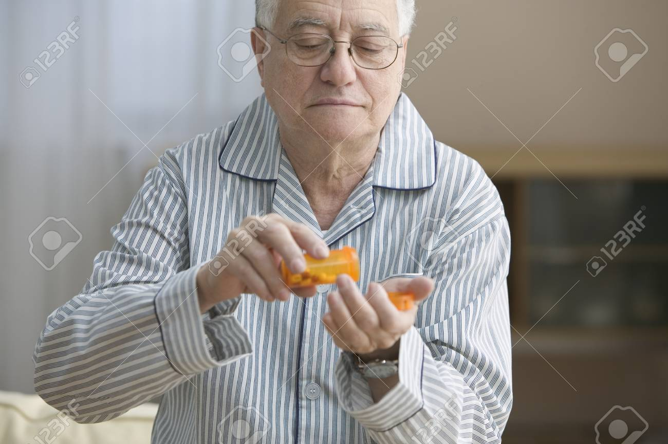Older man shaking out pills into his hand Stock Photo - 16073157