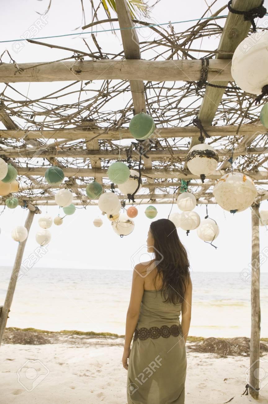 Woman standing beneath awning on beach Stock Photo - 16073475