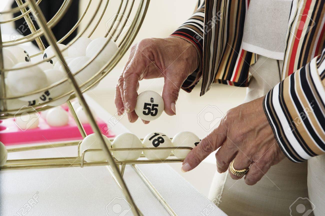 Elderly woman picking up a bingo ball Stock Photo - 16073518