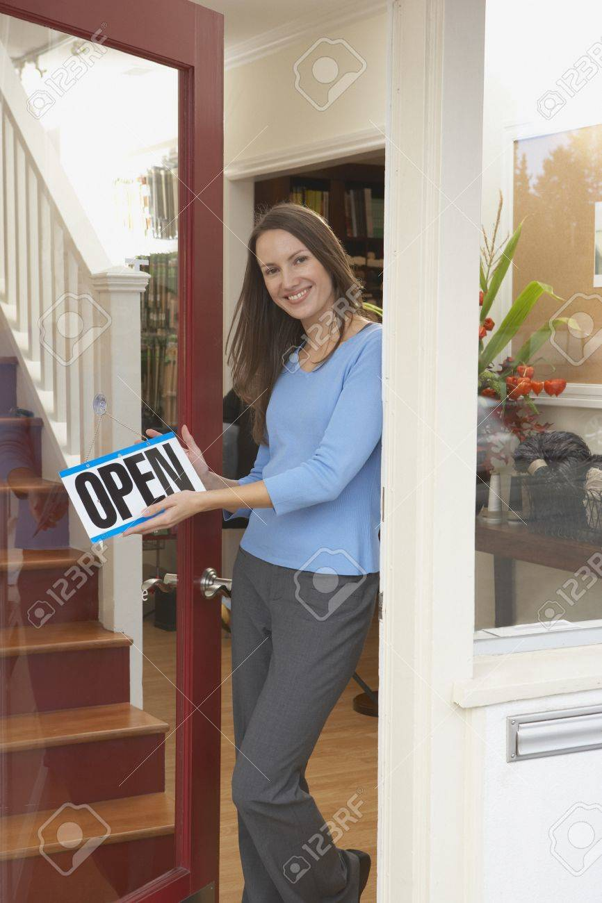 Portrait of woman hanging open sign on shop door Stock Photo - 16073870