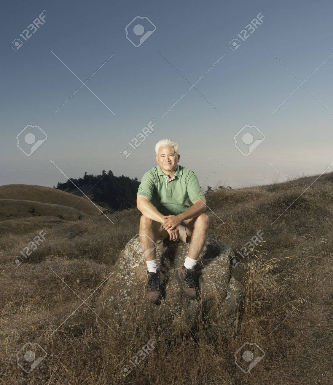 Senior man posing for the camera on a rock Stock Photo - 16089417