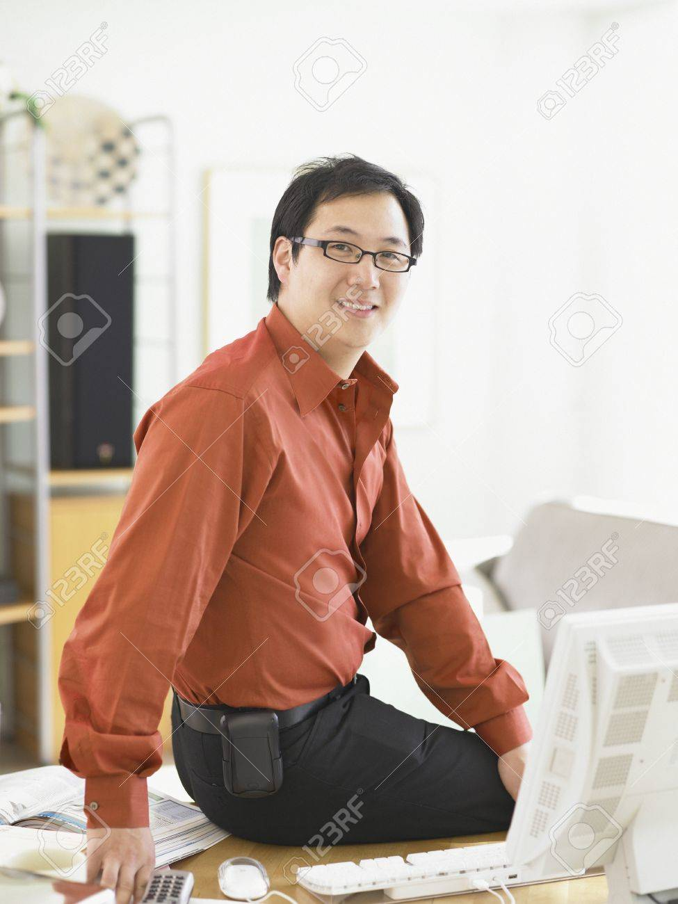 Businessman smiling for the camera at his desk Stock Photo - 16089564