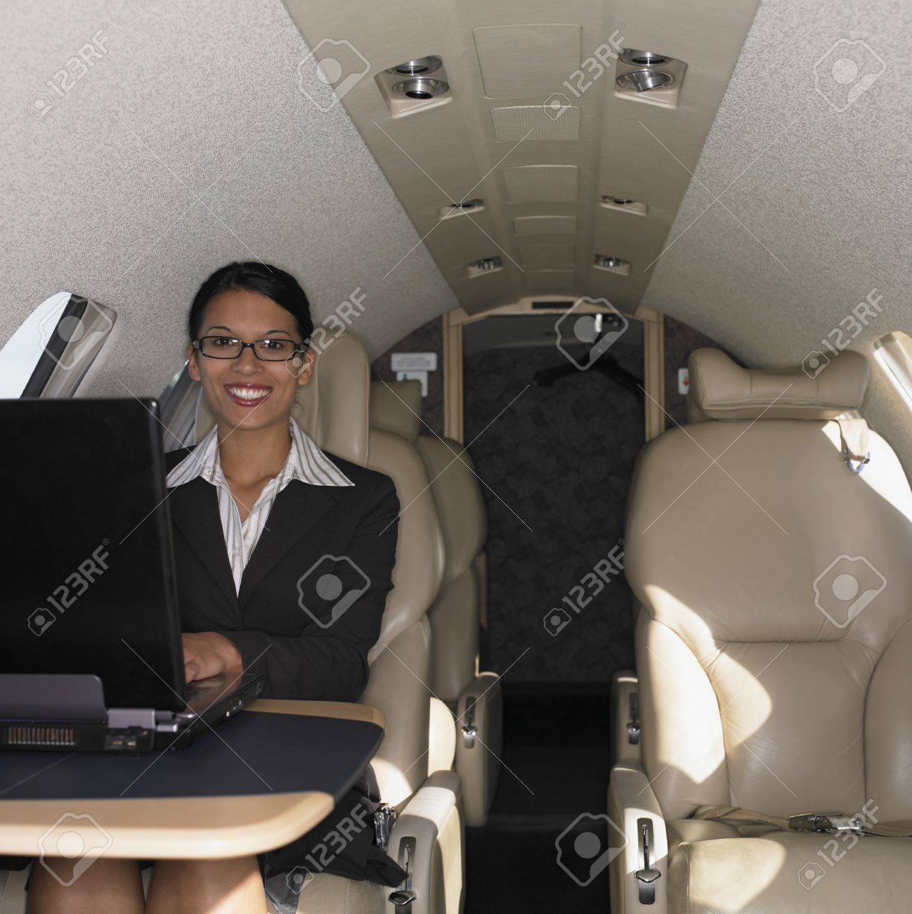Businesswoman working on laptop inside airplane, Perth, Australia Stock Photo - 16090334