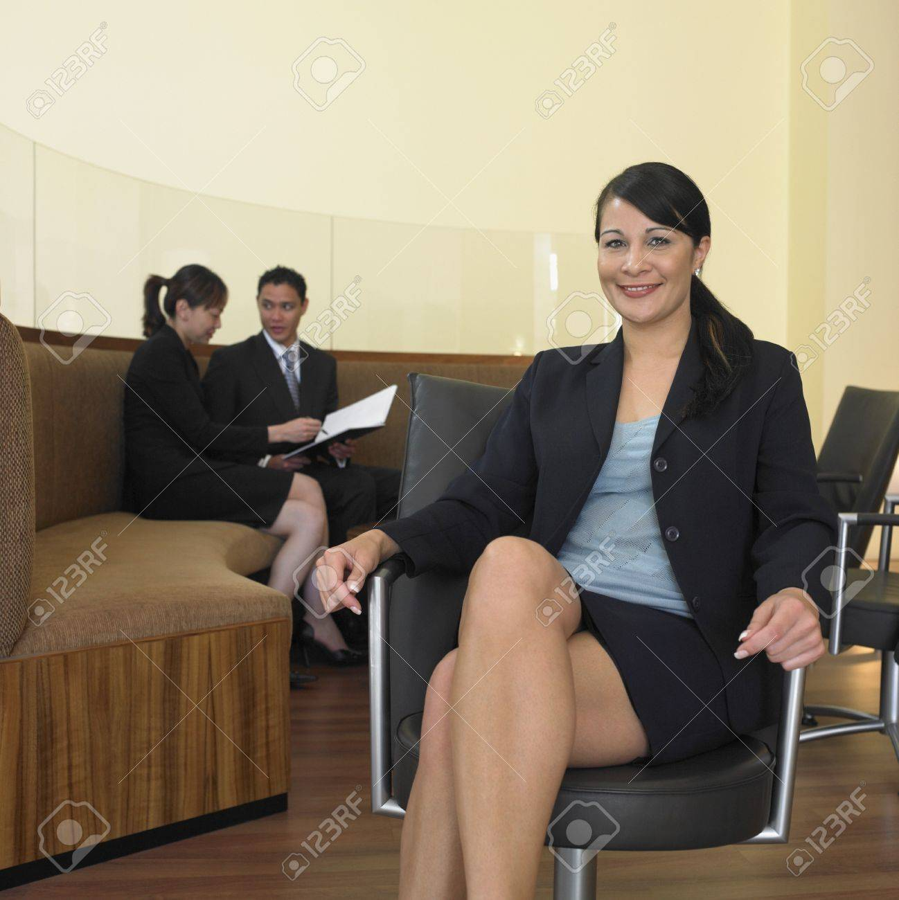 Businesswoman sitting with co-workers in background Stock Photo - 16090393